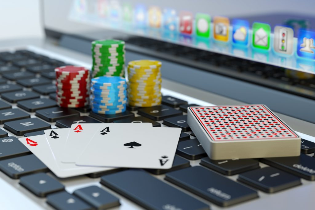 Online poker, virtual casino and gambling concept, four aces, deck of playing cards and colorful chips on computer laptop keyboard